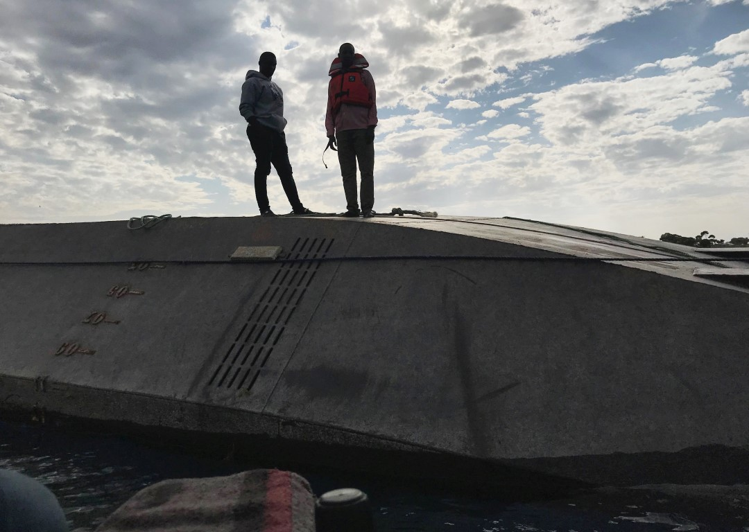 Rescuers stand on the overturned MV Nyerere as they search for bodies off the shores of Ukara...