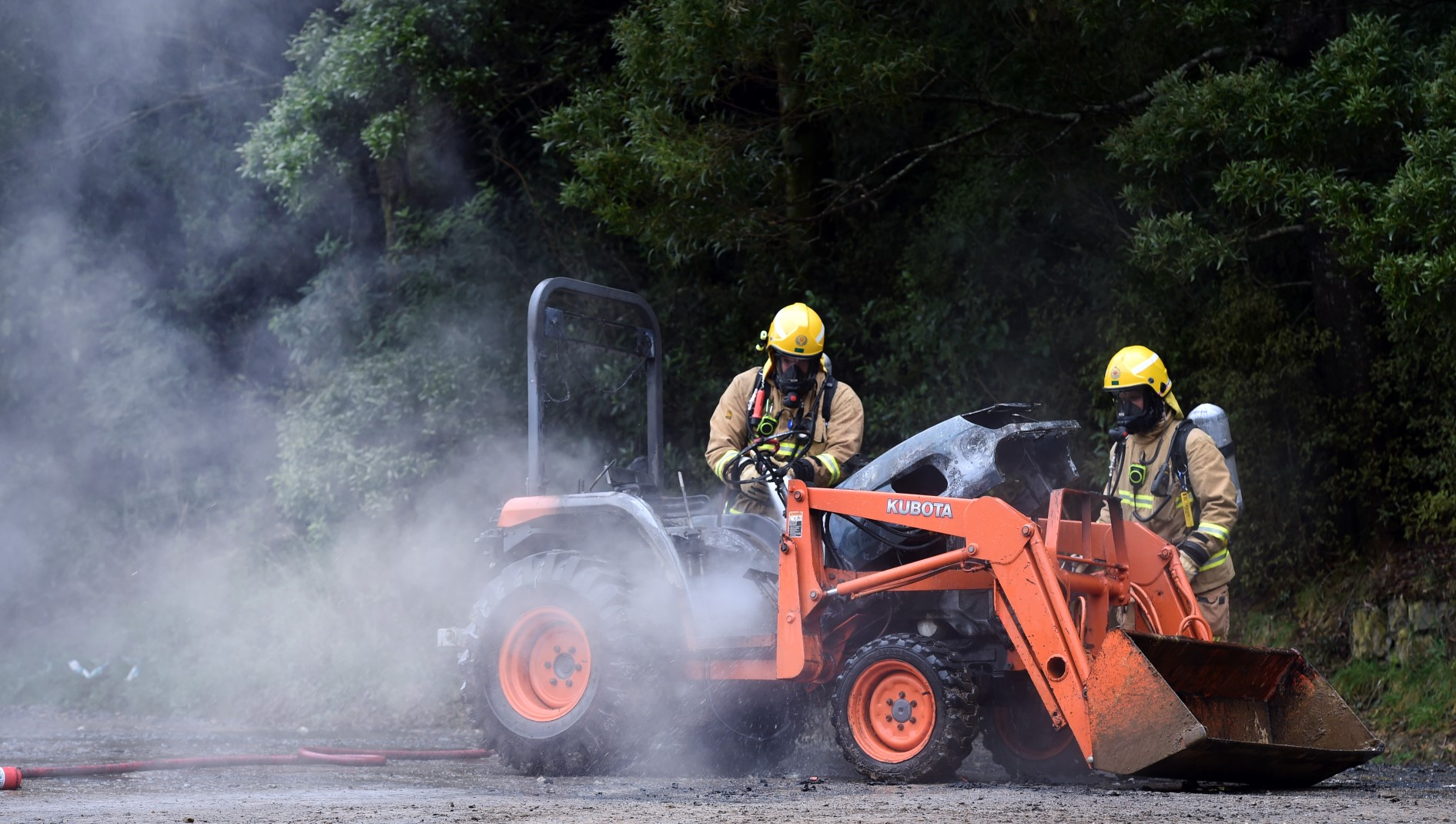 Firefighters extinguish a blaze which started in a tractor this afternoon. Photo: Peter McIntosh