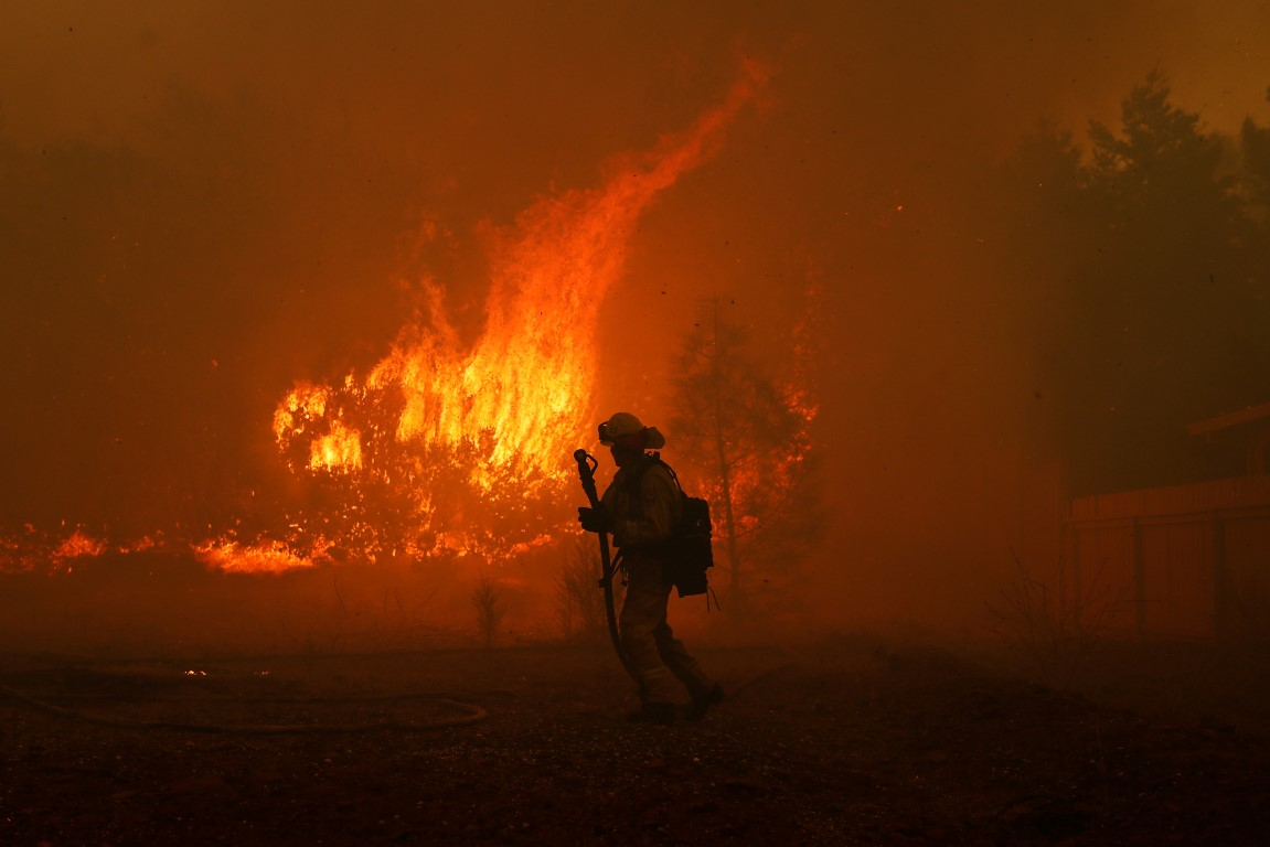 A firefighter monitors a blaze near a home while battling the Camp Fire in Paradise, California....
