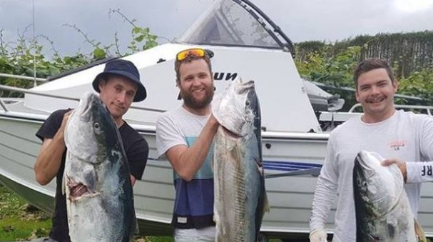 Kevin Lloyd (right) with the kingfish he managed to land despite being attacked by a shark. Photo...