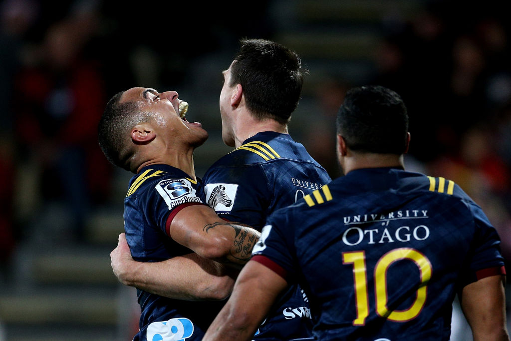 Highlanders fullback Ben Smith (C) celebrates with team-mate Aaron Smith after scoring a try...