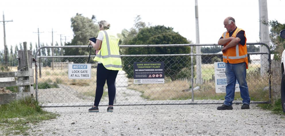 A WorkSafe New Zealand official, watched by another official, examines a gate through which the...