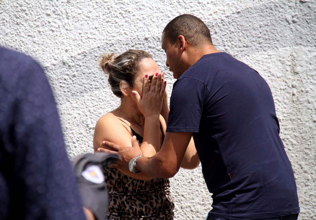 A man comforts a woman outside the school after the shooting. Photo: AP