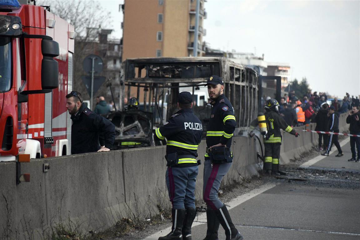 Firefighters and police officers stand by the gutted remains of the bus in San Donato Milanese,...