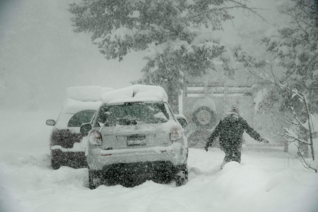 A woman tries to brush snow from her car in Nederland, Colorado. Photo: Getty