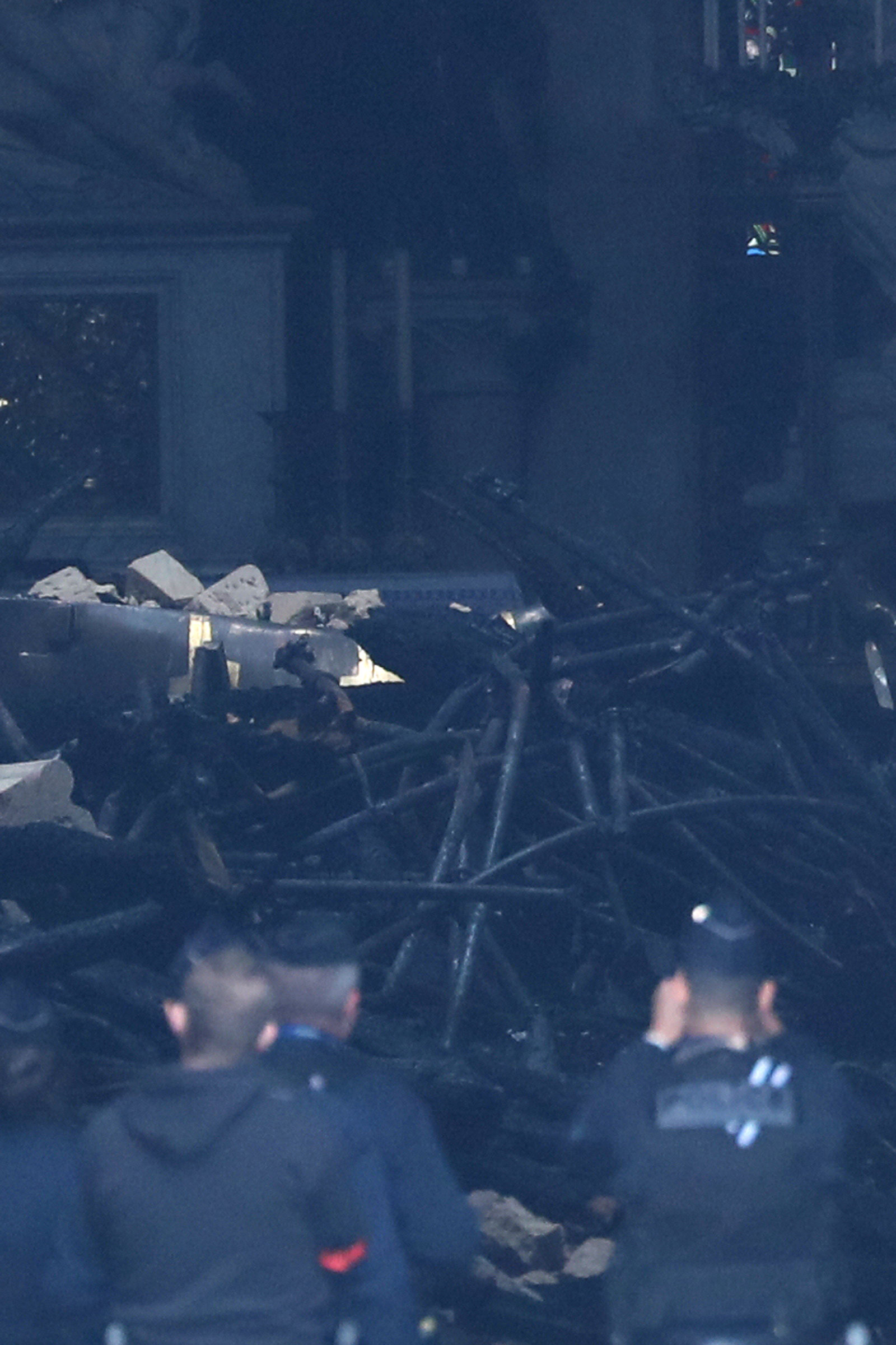 French police look at debris inside Notre-Dame Cathedral after a massive fire devastated large...
