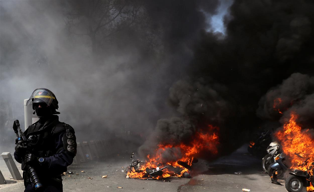A police officer stands next to the burning motorcycles during a demonstration on Act XXIII (the...