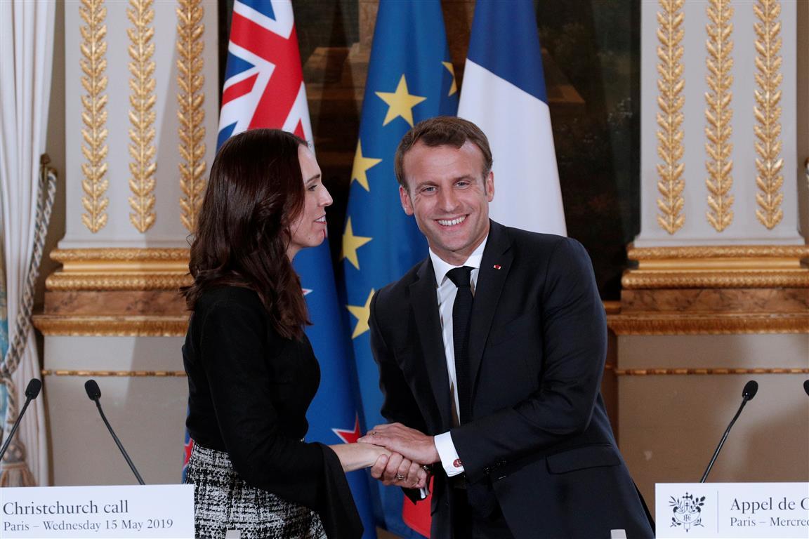 French President Emmanuel Macron greets New Zealand's Prime Minister Jacinda Ardern following...
