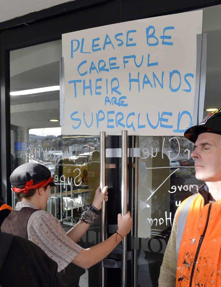 A protester with hands superglued to the front doors of the Dunedin Town Hall. Photo: Gerard O'Brien