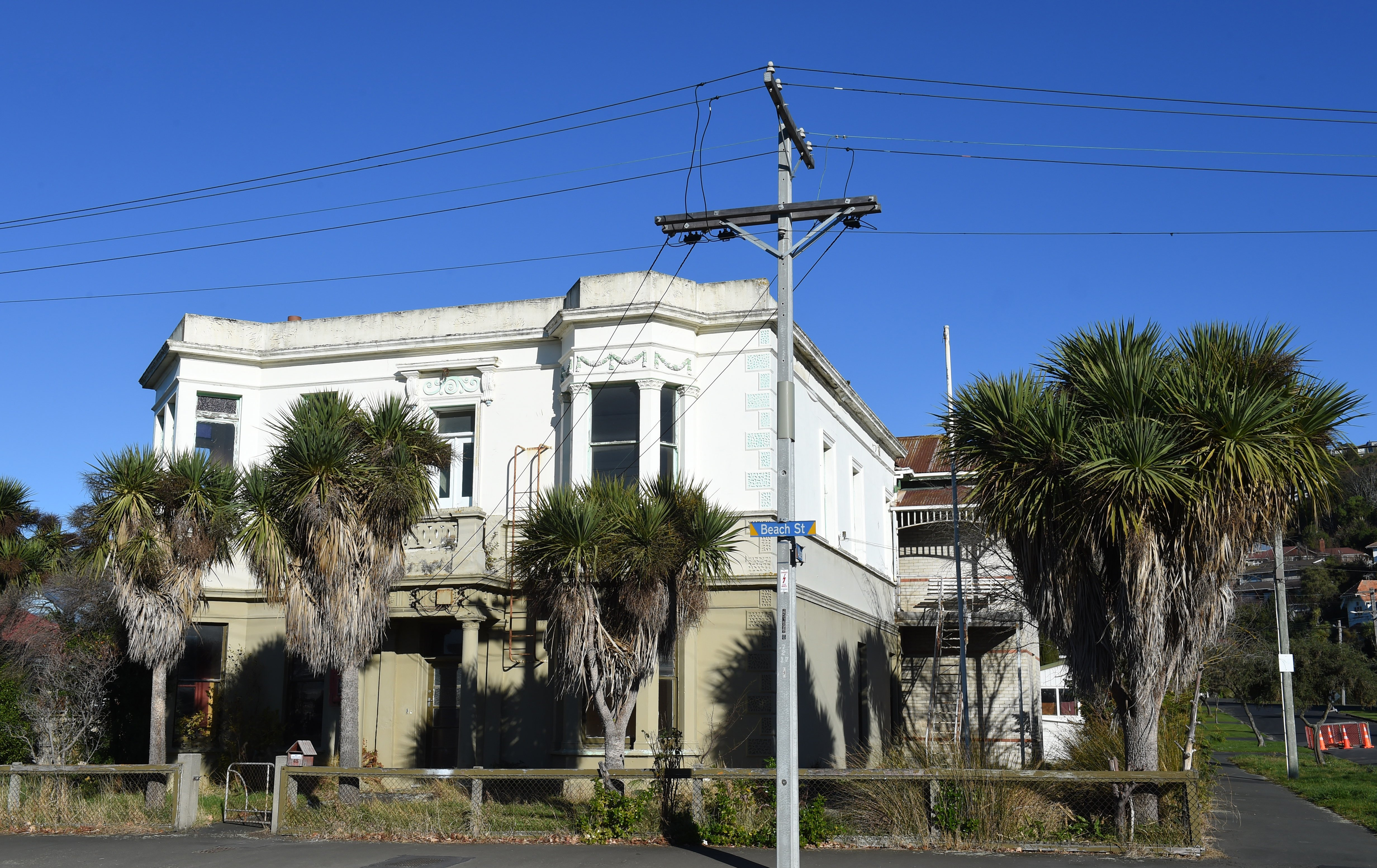 Cabbage trees/ti kouka give this property in Beach St, St Clair in interesting Spanish-American...
