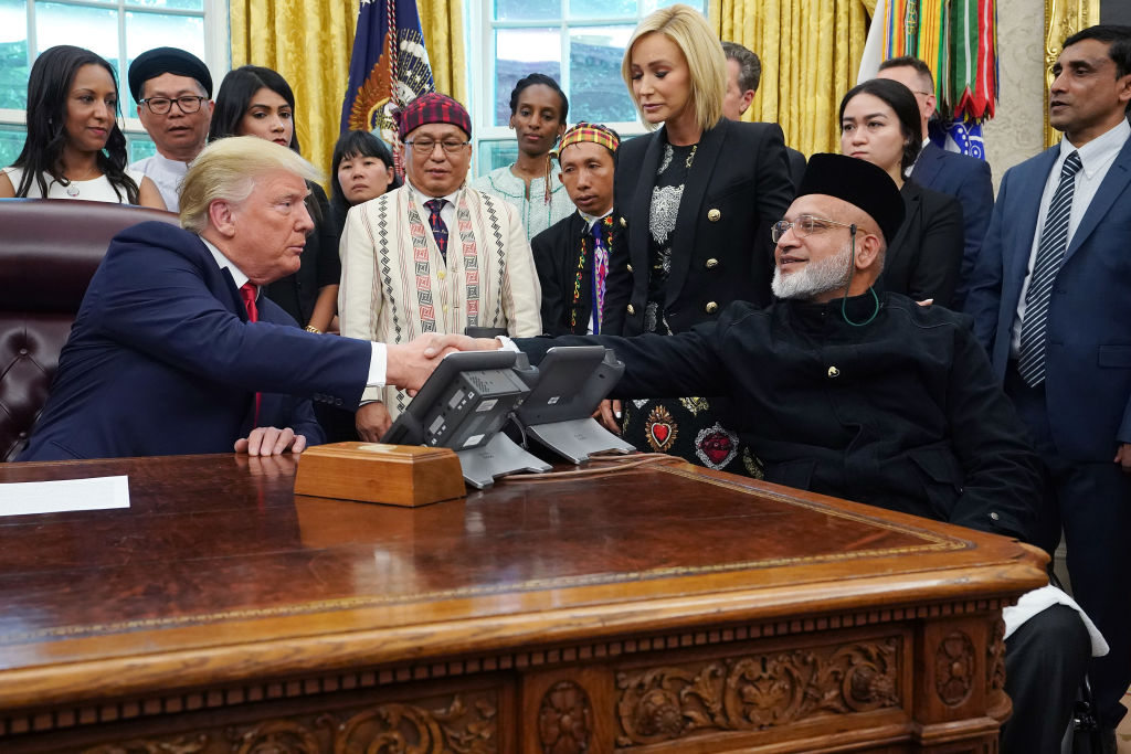 US President Donald Trump shakes hands with Christchurch mosque shooting survivor Farid Ahmed in...