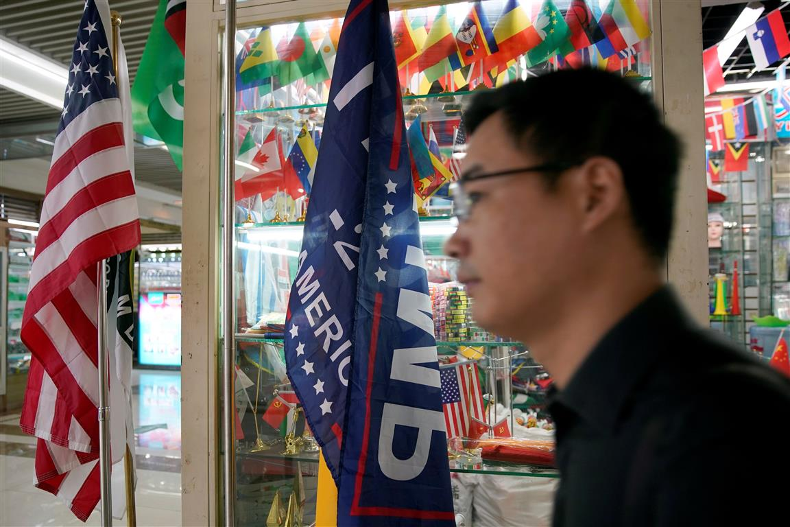 The US flag  and a 2020 re-election campaign flag and are seen in a stall at the Yiwu Wholesale...