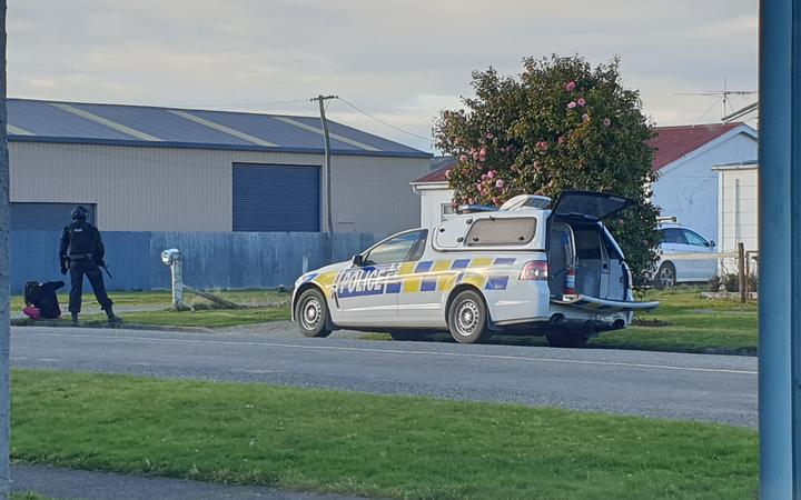 Armed police officers stand guard outside a home in Surrey Street, Gore. Photo: RNZ/ Tim Brown