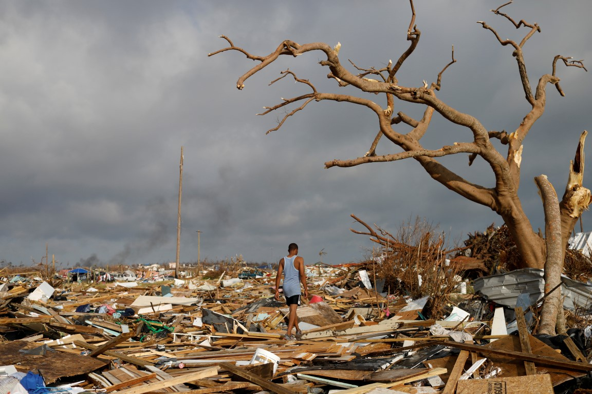 A man walks among debris in the Mudd neighborhood in Marsh Harbour after it was hit by Hurricane...