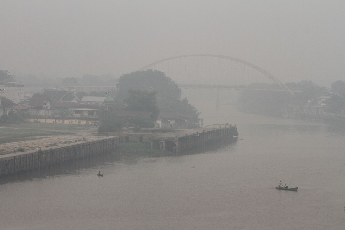 People cross a smog-covered river in Pekanbaru, Riau province, Indonesia. Photo: Antara Foto/Rony...