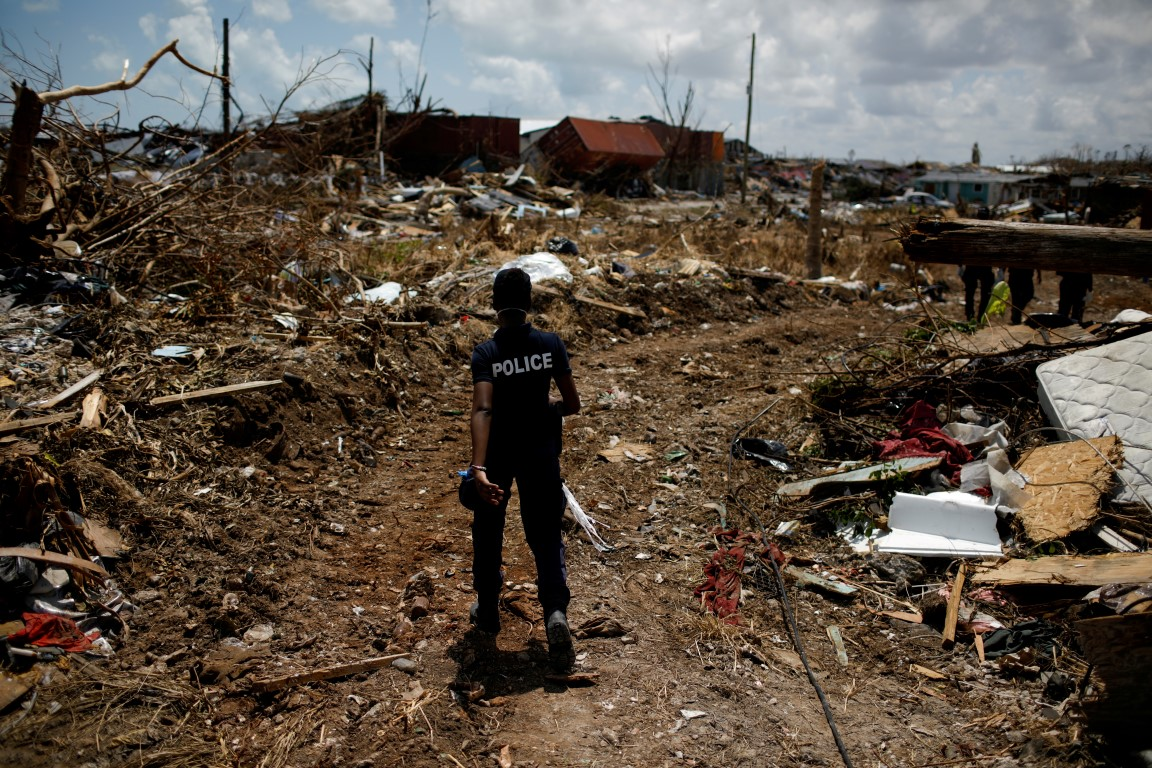 A police officer searches for victims in the destroyed Mudd neighbourhood after Hurricane Dorian...