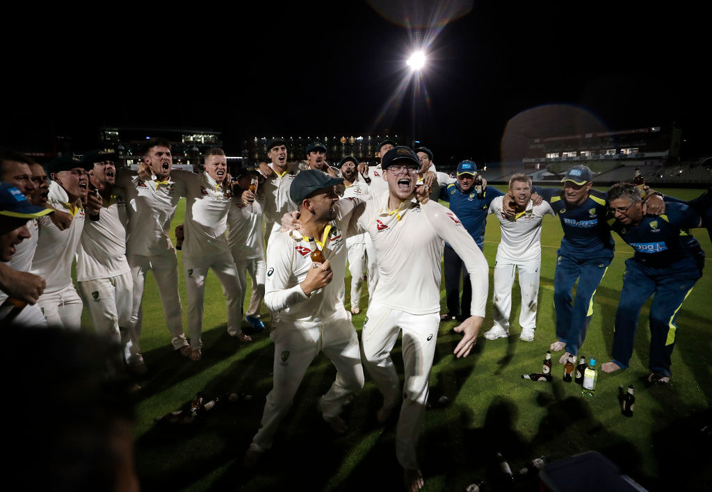 Nathan Lyon and Steve Smith celebrate with teammates after their victory at Old Trafford. Photo:...