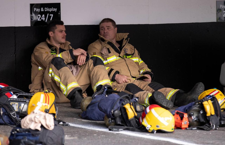 Firefighters take a break from battling the blaze. Photo: NZ Herald