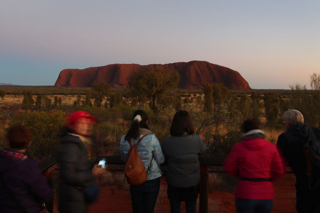 Visitors to Uluru take photos from a viewing area during sunrise. Photo: Getty