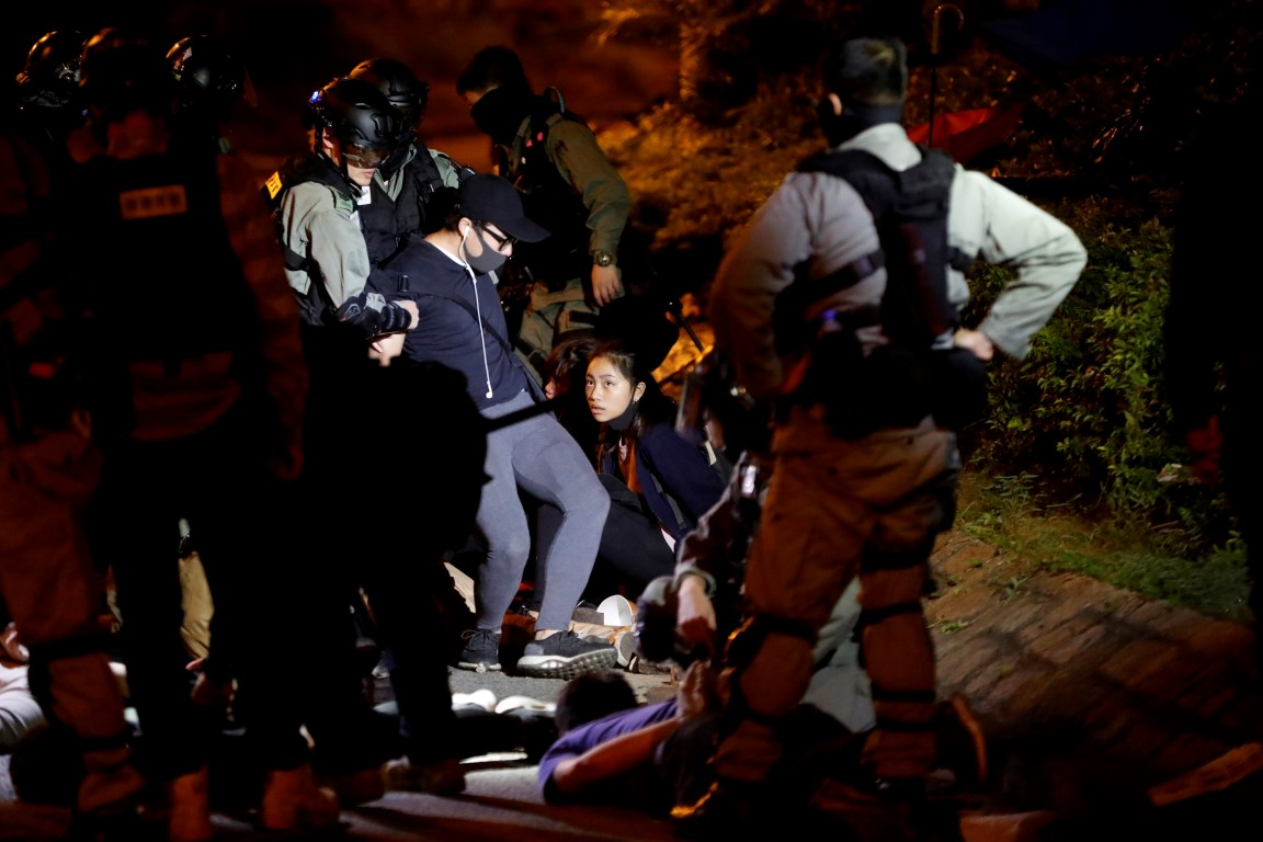 Protesters are detained after trying to leave the Hong Kong Polytechnic University campus. Photo:...