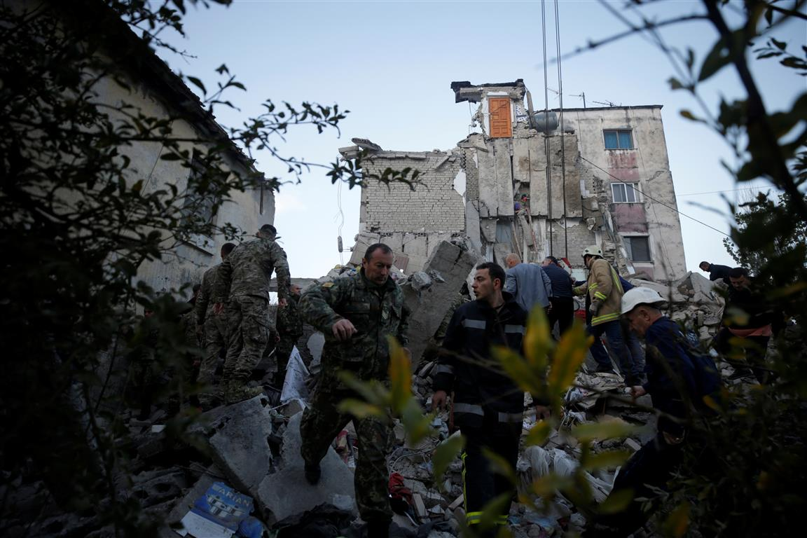 Emergency personnel work near a quake-damaged building in Thumane. Photo: Reuters