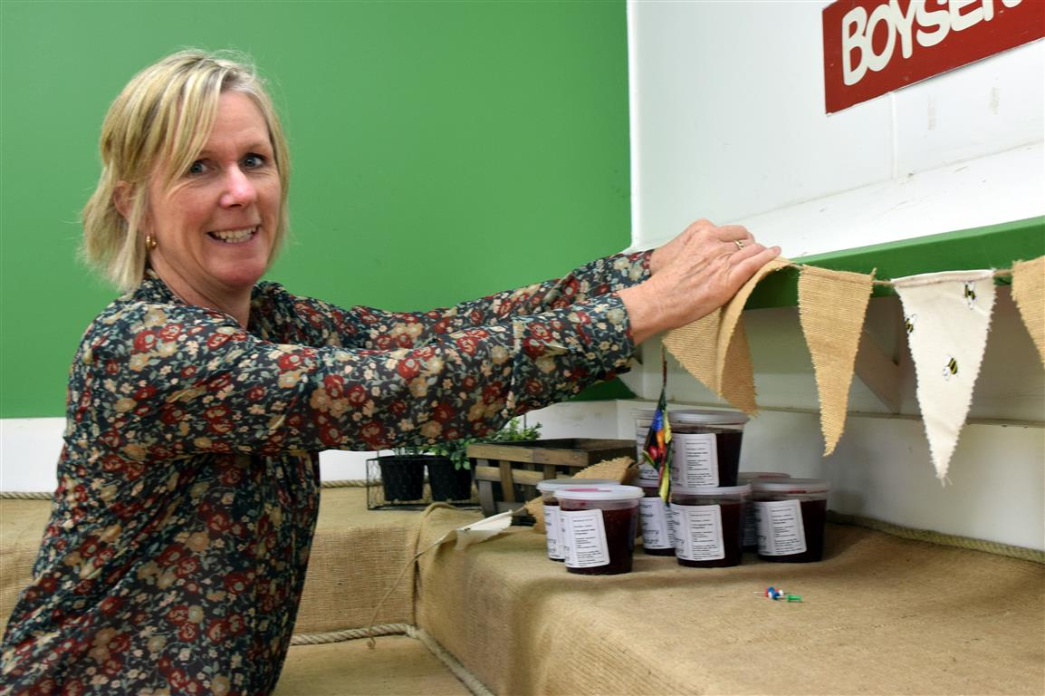 McArthur's Berry Farm co-owner Kaye McArthur hangs bunting in preparation for her shop in Outram...
