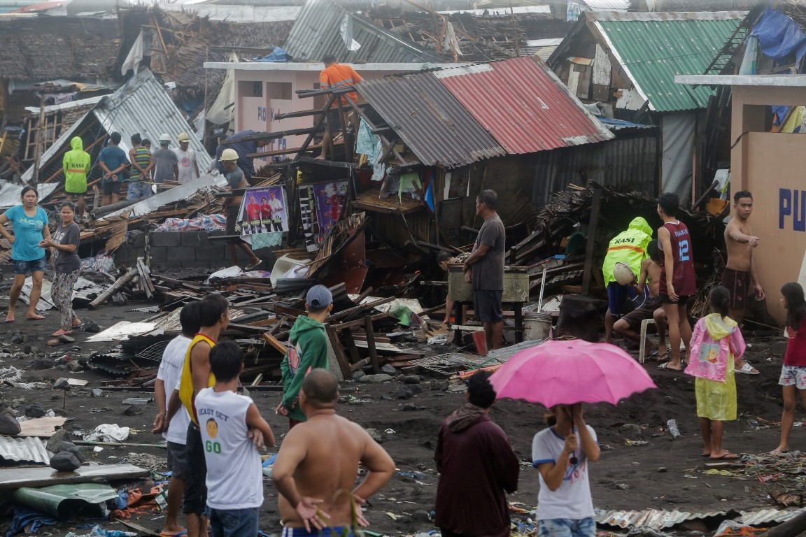 Residents stand among their damaged houses after Typhoon Kammuri hit Legazpi City, Albay, in the...