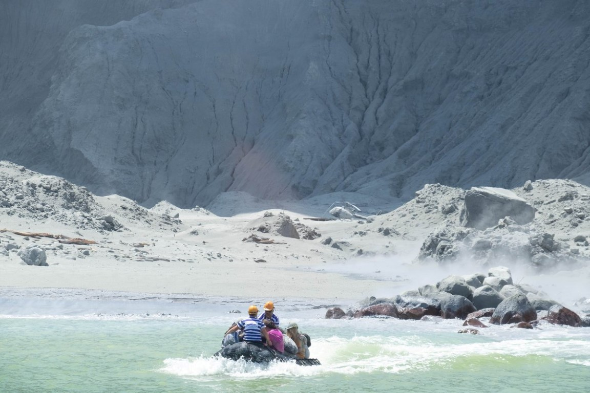 Tour guides evacuate people on a boat shortly after the eruption. Photo: @SCH/via REUTERS
