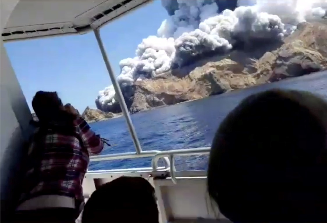 People on a boat watch as smoke billows from White Island. Photo: INSTAGRAM @ALLESSANDROKAUFFMANN...