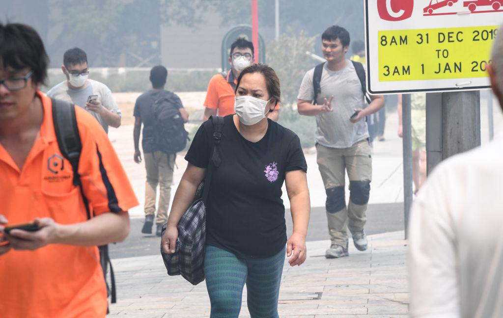 People wear face masks as bushfire smoke haze hangs over Sydney yesterday. Photo: Getty