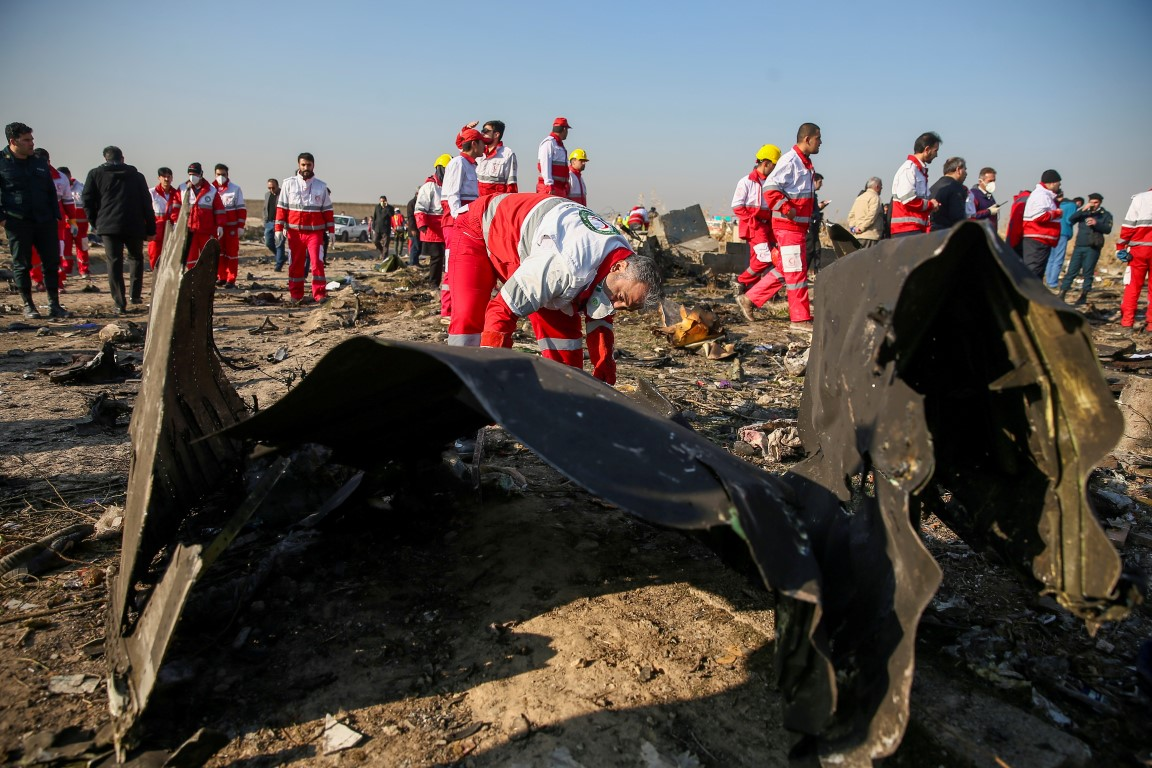 Red Crescent workers check the debris from the crashed plane in the outskirts of Tehran. Photo:...