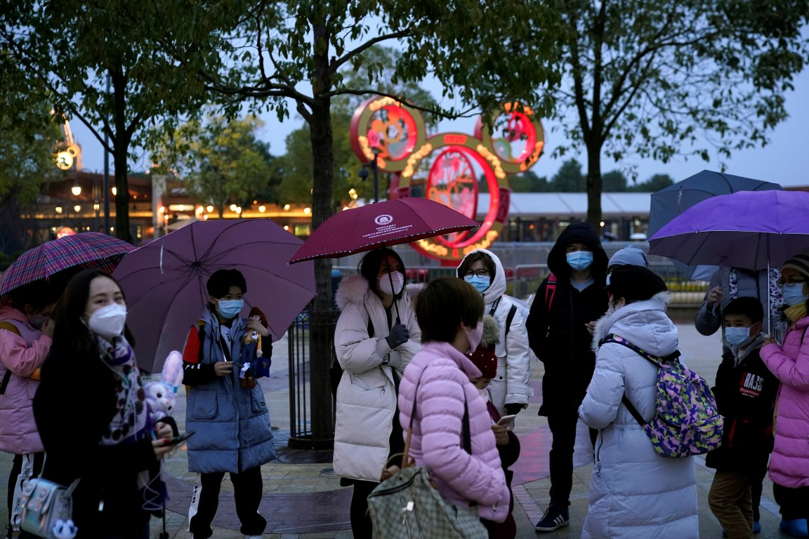Visitors wearing masks outside the Shanghai Disney Resort, which will be closed during the...