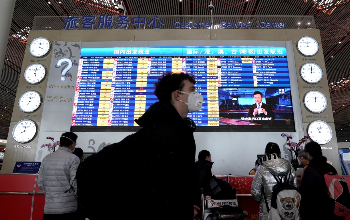 A traveller wearing a mask walks past a departures information board at Beijing International...