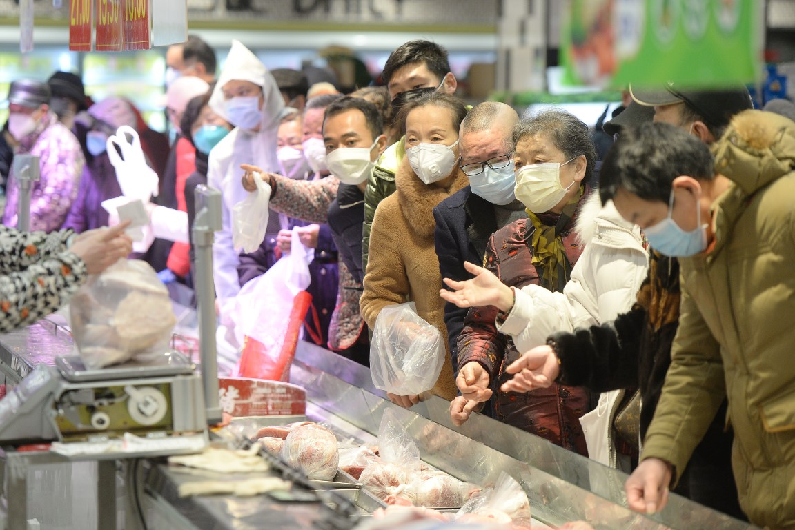 Customers wearing face masks shop inside a supermarket in Wuhan. Photo: Reuters