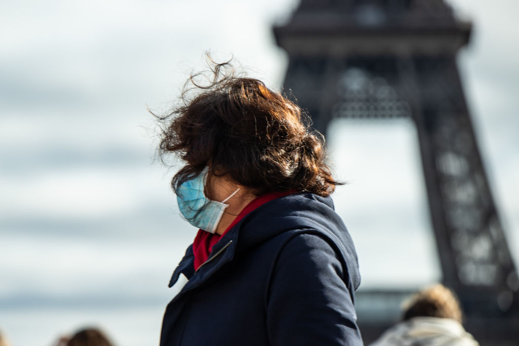 A woman wears a mask in the Trocadero in front the Eiffel Tower in Paris. France has confirmed...