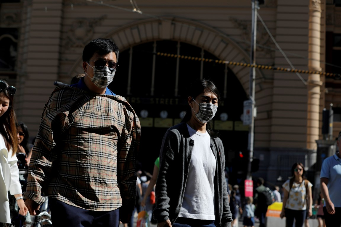 People wearing face masks walk near Flinders Street Station in Melbourne. Photo: Reuters