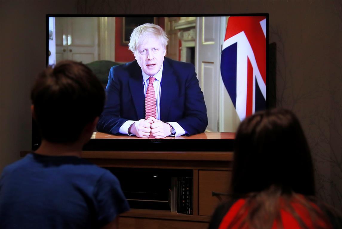 Children in the English town of Hertford watch British Prime Minister Boris Johnson's coronavirus...