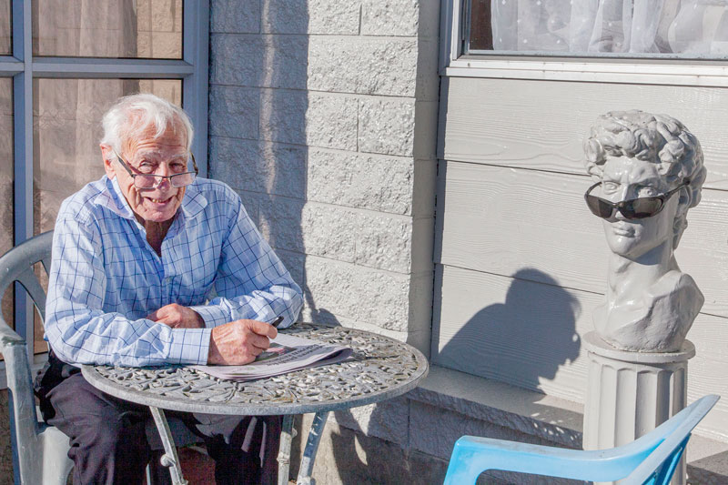 """Enjoying the sun with a friend on Richill St, Belfast. """"He doesn't talk much, and his jokes are..."""