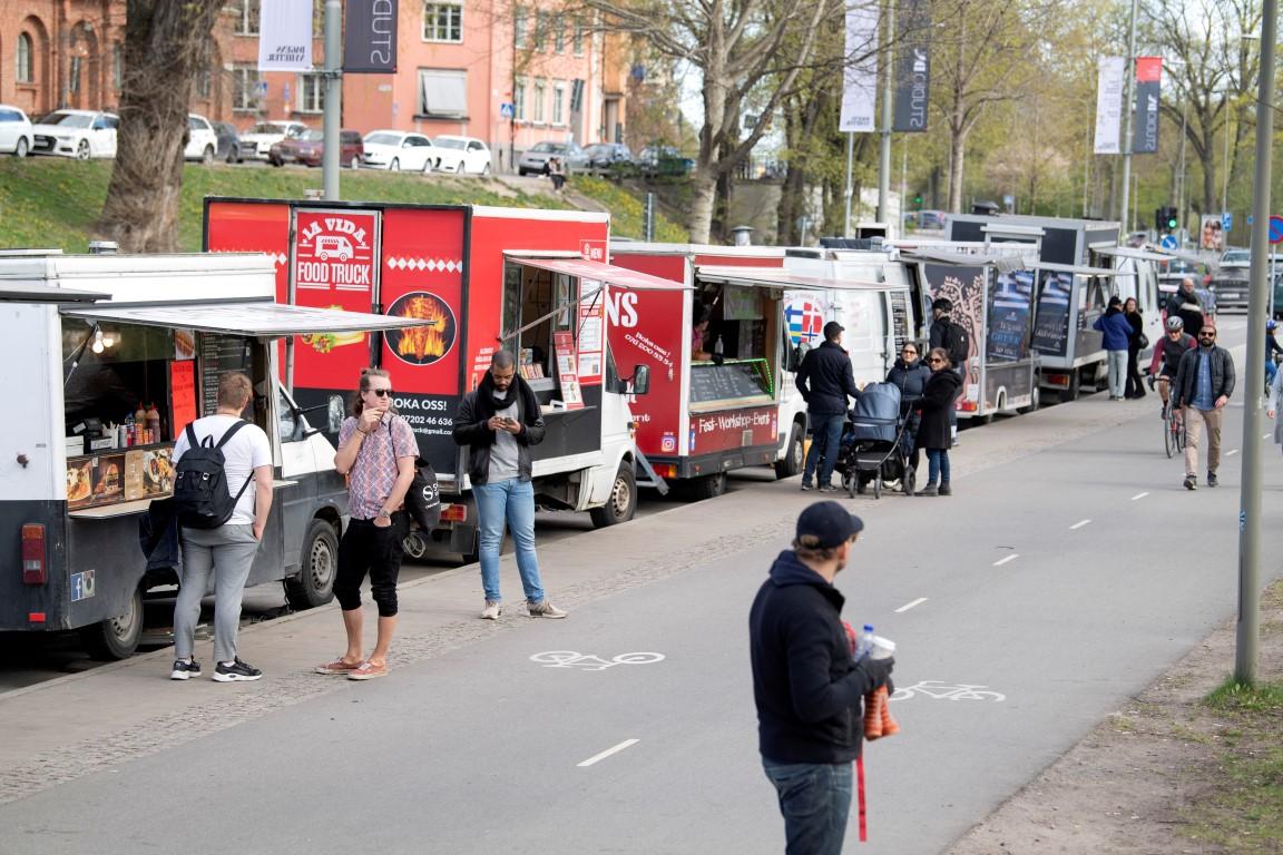 People buy food from food trucks amid the outbreak of the coronavirus disease in Stockholm,...