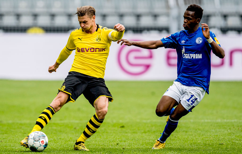 Lukasz Piszczek (left) of Borussia Dortmund is challenged by Rabbi Matondo of FC Schalke 04  on...