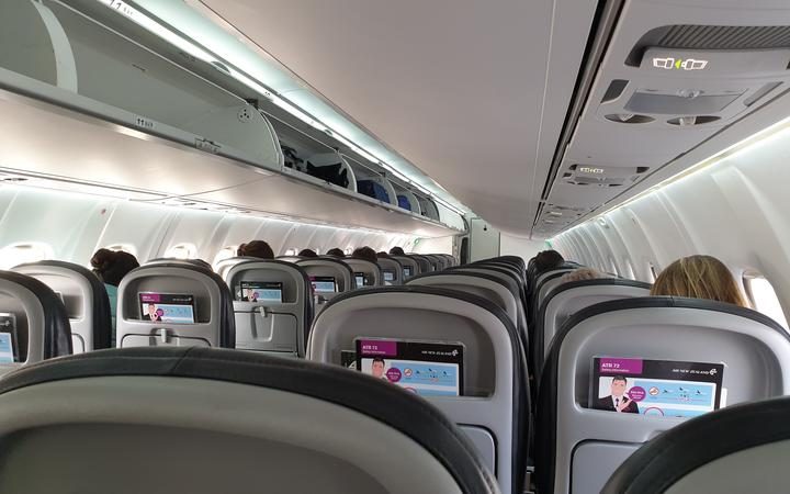 Passengers sitting at a distance from each other on an Air New Zealand flight from Christchurch...