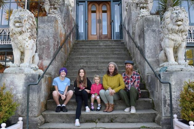 Sitting on the steps of an entrance to Larnach Castle are parents Carmen Howell and Tim Ryan and...