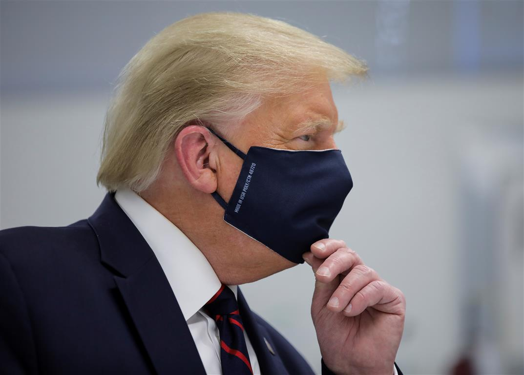 US President Donald Trump wears a protective face mask during a tour of the Fujifilm Diosynth...