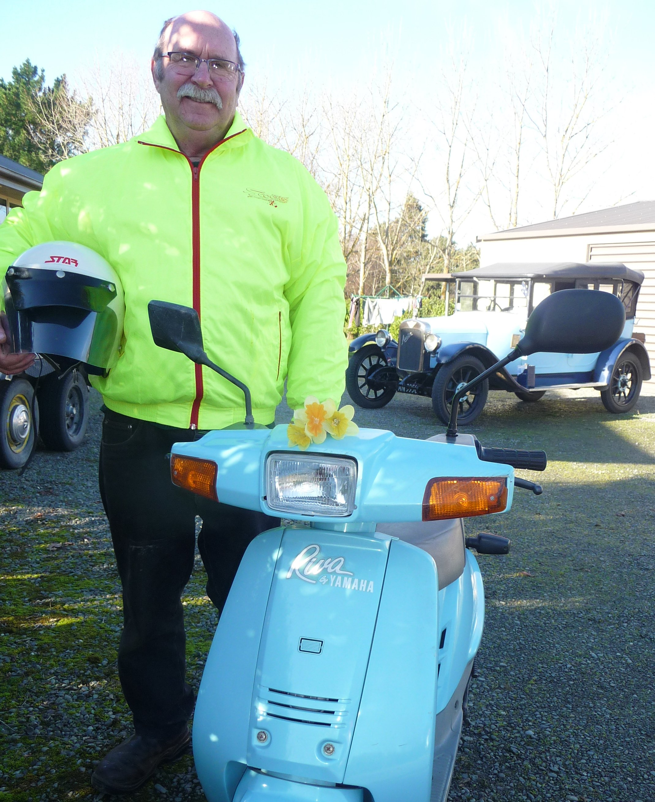 David Oakley with his 49cc Yamaha Riva Razz and in the back ground his 1926 Austin 12. Photo:...
