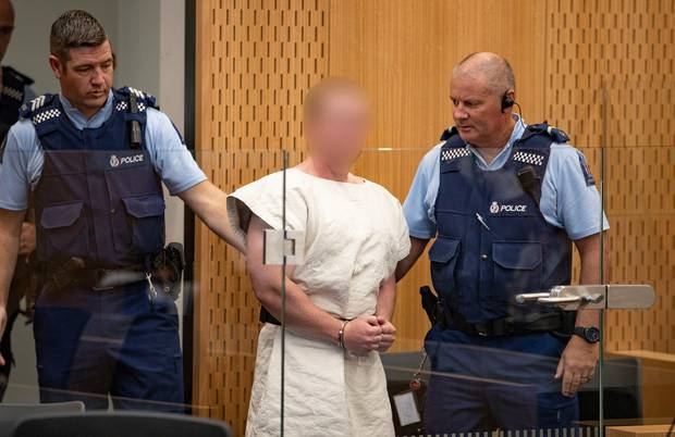 The man charged in relation to the Christchurch massacre is led into the dock for his appearance,...