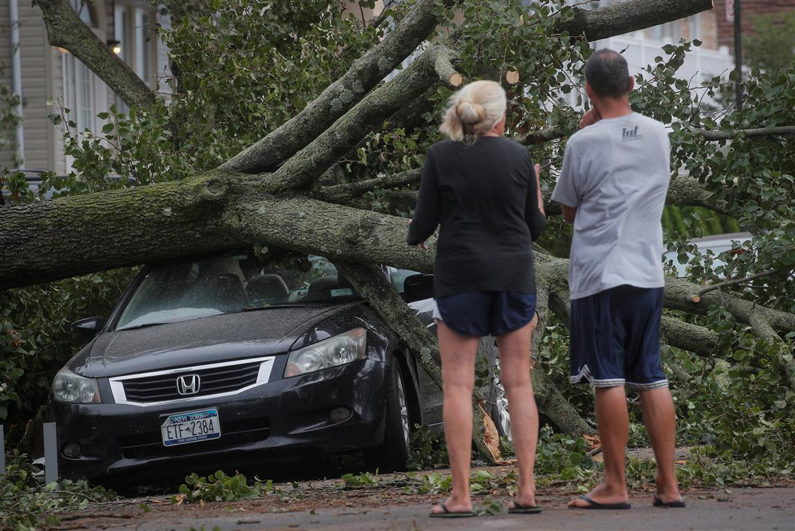 People look at a fallen tree on a car in the aftermath of Tropical Storm Isaias in the Rockaway...