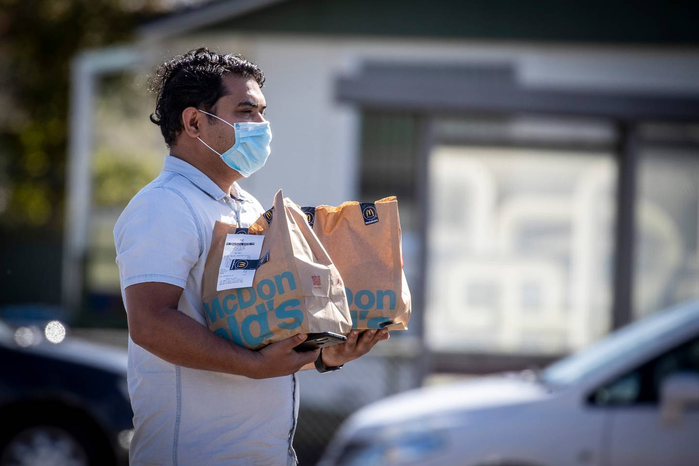 An UberEats delivery driver collects a meal from McDonald's in April. Photo: Michael Craig / NZH