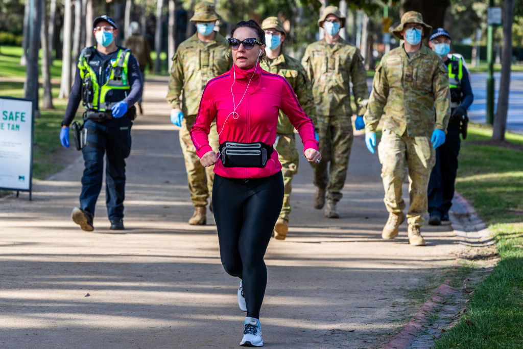 A woman jogs near Australian Defence Force personnel and protective service officers as they...