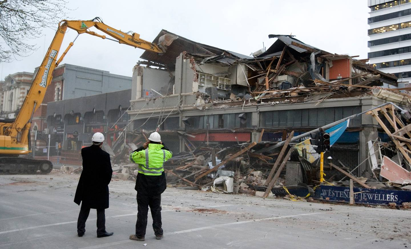 Insurance and demolition workers watch as the earthquake-damaged building on the corner of...
