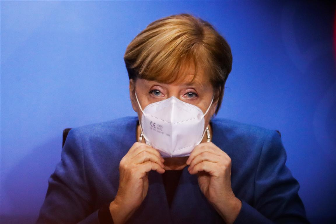 German Chancellor Angela Merkel puts on her face mask at the end of a news conference in Berlin....